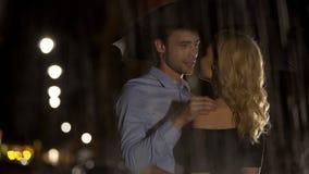 Соедините любовников смотря один другого, прячущ от дождя под зонтико стоковое изображение rf