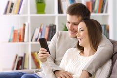 Соедините наблюдая средства массовой информации на умном телефоне сидя дома стоковое изображение