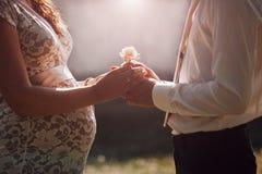 Соедините надеяться ребенка держа руки при розовый цветок смотря на один другого Стоковые Фотографии RF