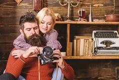 Соедините объятия в деревянном винтажном интерьере Человек с бородой, фотограф на занятой стороне держит старомодную камеру Соеди стоковое фото rf