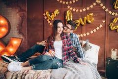 Соедините объятия на кровати в спальне с украшением Стоковое фото RF