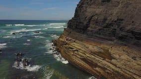 Соедините положение на одичалом пляже с скалами позади, Португалия акции видеоматериалы