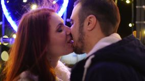 Соедините поцелуев любовников совместно Света рождества на предпосылке Хорошее настроение, потеха, любовь, счастливая концепция Н сток-видео