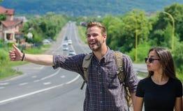 Соедините путешественников человека и девушки путешествовать на предпосылке природы дороги края Перемещение autostop Автостопщики стоковая фотография