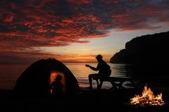 Соедините располагаться лагерем с гитарой и лагерным костером на пляже Стоковые Изображения
