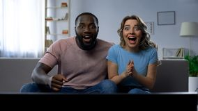 Соедините смотреть спичку спорт на доме ТВ, празднуя победу, успешная игра стоковое изображение