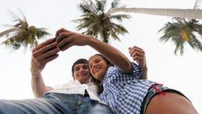 Соедините фото selfie взятия на телефоне клетки умном под пальмами, Стоковая Фотография RF