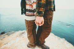 Соедините человека и женщины держа руки стоя на скале Стоковая Фотография