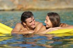 Соедините flirting плавать на раздувную кровать стоковые изображения rf
