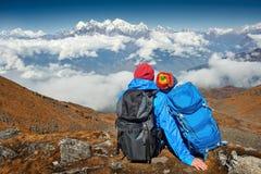 Соедините Hikers при рюкзаки смотря смотрящ na górze mounta Стоковая Фотография RF