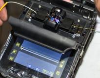 Соединяя оптический кабель волокна с Splicer сплавливания стекловолокна оборудует профессиональный инструмент стоковая фотография