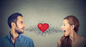 Соединение влюбленности Женщина человека говоря друг к другу красное сердце in-between стоковое фото rf