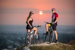 Соедините велосипедиста с горными велосипедами на холме на заходе солнца Стоковое Изображение RF