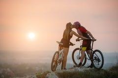 Соедините велосипедиста с горными велосипедами на холме на заходе солнца Стоковое Изображение