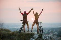 Соедините велосипедиста с горными велосипедами на холме на заходе солнца Стоковые Фотографии RF