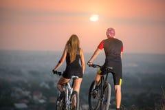Соедините велосипедиста с горными велосипедами на холме на заходе солнца Стоковые Фото