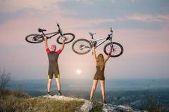 Соедините велосипедиста с горными велосипедами на холме на заходе солнца Стоковые Изображения RF