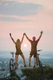 Соедините велосипедиста с горными велосипедами на холме на заходе солнца Стоковые Изображения