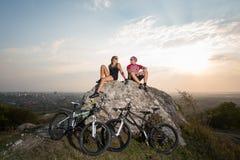 Соедините велосипедистов сидя на каменных близко велосипедах в вечере Стоковые Изображения RF
