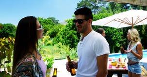 Соедините взаимодействовать пока имеющ бутылку пива около poolside видеоматериал