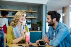 Соедините взаимодействовать пока имеющ чашку кофе и milkshake стоковые изображения rf