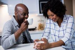 Соедините взаимодействовать друг с другом пока имеющ кофе в кухне стоковая фотография