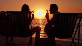 Соедините выпивая пар во время захода солнца на пляже