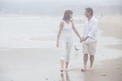 Соедините говорить пока идущ на туманный пляж усмехаясь на каждом ot Стоковые Изображения