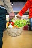 Соедините держать корзину овощей в супермаркете Стоковое Изображение