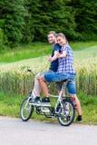 Соедините ехать тандемный велосипед совместно в стране Стоковое Фото