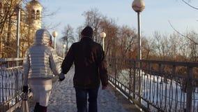 Соедините идти держащ руки на малом мосте полный замков влюбленности съемка steadicam 4K акции видеоматериалы