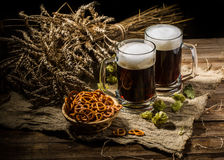 Соедините кружку пива с хмелем и кренделями на linen ткани Стоковое Фото