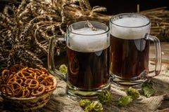 Соедините кружку пива с хмелем и кренделями на linen ткани Стоковые Изображения
