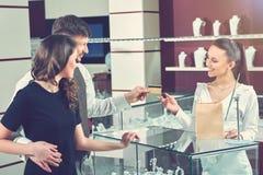 Соедините покупая ювелирные изделия в магазине и оплачивать с карточкой Стоковое фото RF