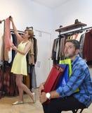 Соедините покупки вместе с пробуренный ждать человека разочарованному пока девушка приспосабливает одежды стоковая фотография