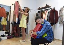 Соедините покупки вместе с пробуренный ждать человека разочарованному пока девушка приспосабливает одежды стоковое фото rf