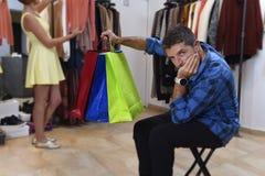 Соедините покупки вместе с пробуренный ждать человека разочарованному пока девушка приспосабливает одежды стоковые изображения rf