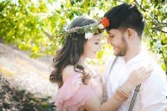 Соедините портрет девушки и парня ища платье свадьбы, розовое летание платья с венком цветков на ее голове на backg стоковое изображение rf