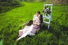 Соедините портрет девушки и парня ища платье свадьбы, розовое летание платья с венком цветков на ее голове на backg Стоковые Изображения