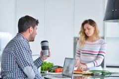 Соедините положение и усаживание на кухне пока усмехаться и человек читая газету и держа кружку перед работой Стоковые Фото