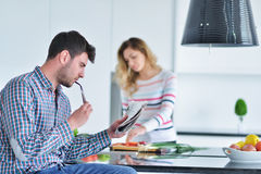 Соедините положение и усаживание на кухне пока усмехаться и человек читая газету и держа кружку перед работой Стоковое Изображение RF