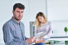 Соедините положение и усаживание на кухне пока усмехаться и человек читая газету и держа кружку перед работой Стоковые Фотографии RF