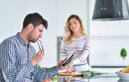 Соедините положение и усаживание на кухне пока усмехаться и человек читая газету и держа кружку перед работой Стоковое Изображение