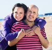 Соедините радостно обнимать один другого и наслаждаться пляжем стоковое фото