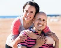 Соедините радостно обнимать один другого и наслаждаться пляжем стоковое изображение