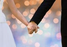 Соедините руки держа пар свадьбы с сверкная светлой предпосылкой bokeh Стоковое Изображение RF