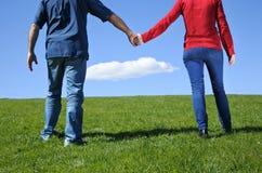 Соедините руки и прогулки владением на зеленой траве к горизонту стоковые изображения