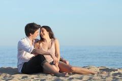 Соедините сидеть и смеяться над на песке пляжа стоковые фотографии rf