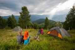 Соедините сидеть на зеленой траве около лагерного костера, шатров, рюкзаков Стоковая Фотография RF