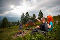 Соедините сидеть на зеленой траве около лагерного костера, шатров, рюкзаков Стоковые Фотографии RF